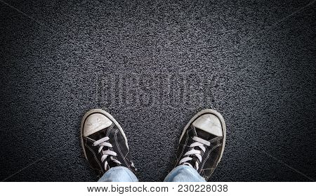 A Teenager In Jeans And Canvas Shoes Standing On Asphalt Road With Copy Space. Concept Of Standing A