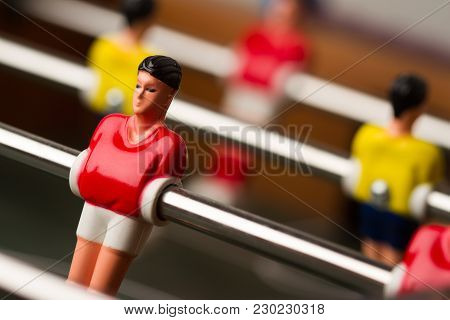 Horizontal Closeup With Selective Focus Of Red Shirt Player Figurine On Foosball Table Soccer Game