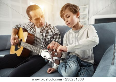 Playing Together. Attractive Joyful Well-built Man Holding The Guitar And Teaching His Son Playing T