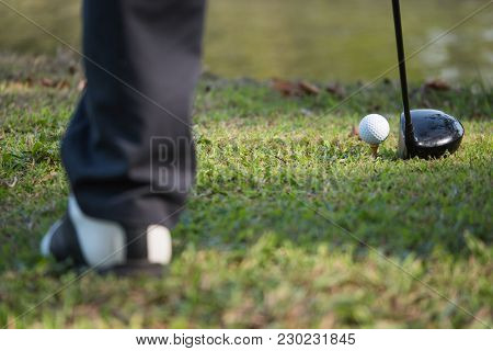 Close Up Of Golf Ball On A Tee With The Driver Positioned Ready To Hit The Ball.
