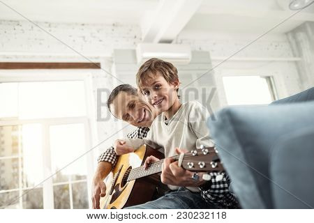 Good Mood. Handsome Smiling Fair-haired Boy Learning To Play The Guitar While Sitting On The Couch A