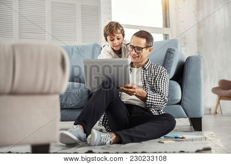 My Dear Son. Handsome Cheerful Dark-haired Father Wearing Glasses And Showing Photos On The Laptop T