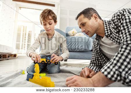 Playing Together. Nice Concentrated Fair-haired Boy Playing With His Erector Set And His Daddy Sitti