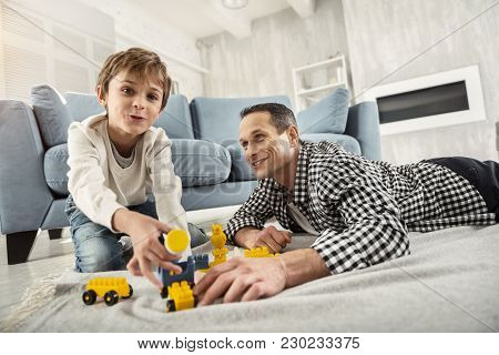 Best Daddy. Good-looking Joyful Fair-haired Boy Playing With His Erector Set And His Daddy Sitting N