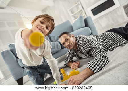 Happy Childhood. Attractive Inspired Fair-haired Boy Playing With His Erector Set And His Daddy Lyin