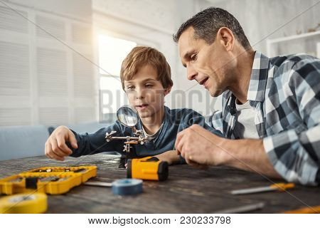 Teaching My Son. Handsome Concentrated Dark-haired Man Showing Instruments To His Son While Sitting