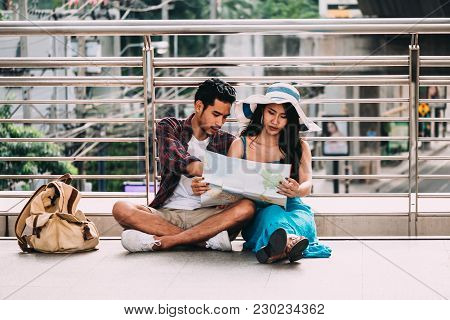 Couple Asian Travelers Are Sitting On City Street And Looking At Interesting Places To Travel From P