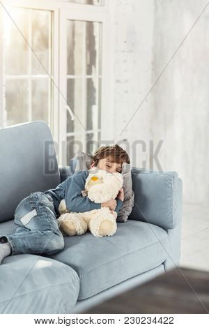 Sweet Dreams. Adorable Little Fair-haired Boy Hugging His Favourite Nice Toy And Lying On The Sofa W