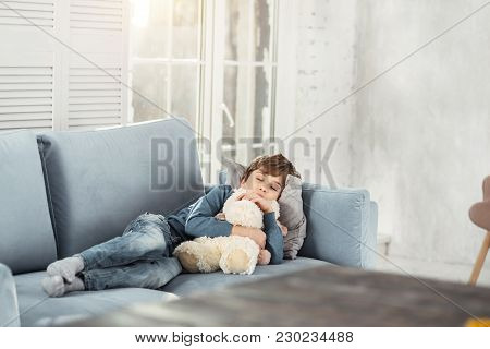 Daydream. Cute Little Fair-haired Boy Hugging His Favourite Nice Toy And Lying On The Comfy Sofa Whi