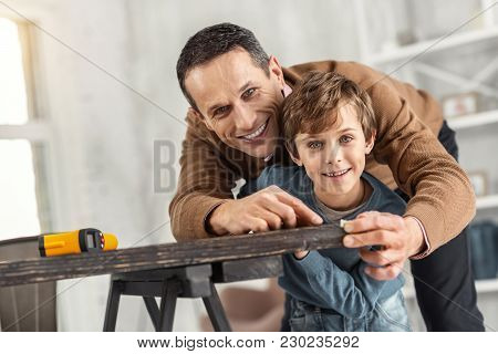 Caring Father. Attractive Exuberant Little Fair-haired Boy Holding A Measuring Tape And Measuring Th