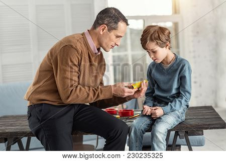 Teaching Process. Handsome Concentrated Dark-haired Daddy Showing Instruments To His Son While Sitti