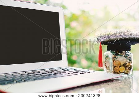 Computer Laptop And Square Academic Cap With The Glass Jar Of Coin Against Blurred Natural Green Bac