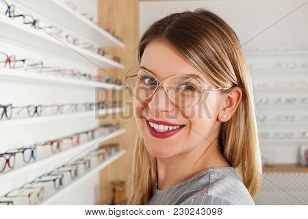 Smiling Young Woman Choosing Eyeglass Frame In An Optical Store