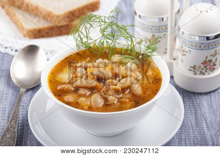 Soup Of White Bean In A White Plate, Bread And Spices In The Background