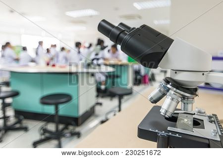 Biology Or Chemistry Science Class Study With Microscope And Blur Background Of School Student Group
