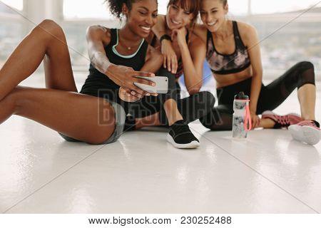Happy Women Taking Selfie In Fitness Studio. Three Female Friends In Healthclub Taking Selfie With M