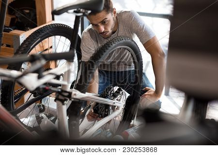 Man Working On A Bicycle Wheel In A Repair Shop. Worker Fixing A Bicycle Wheel In Workshop.
