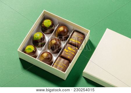 Assortment Of Luxury Bonbons In Box With Copy Space On Green Background. Exclusive Handmade Chocolat