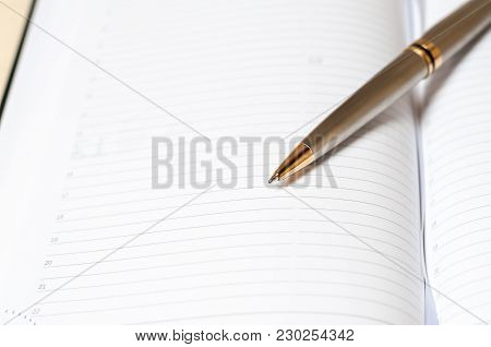 A Steel Pen And An Open Notebook. Reservation Concept. Selective Focus On The Tip Of The Ballpoint P