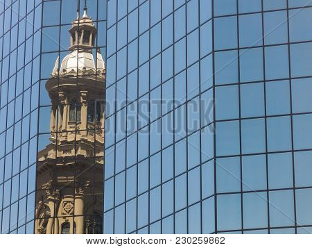 Reflection In A Glass Building Of The Metropolitan Cathedral Of Santiago, In The Armas Square. It Is