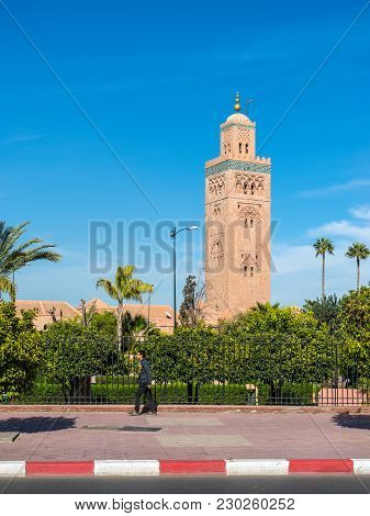 Marrakesh, Morocco - December 8, 2016: A Pedestrian In The Background Of The Koutoubia Mosque (kutub
