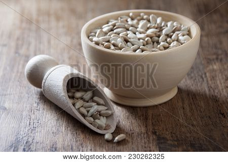 Sunflower Seeds In A Wooden Bowl And A Wooden Spoon On A Wooden Table
