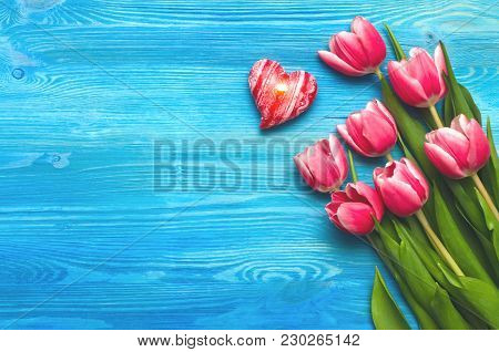 Tulip Flowers And Burning Heart Shape Candle On Blue Wooden Table Board Romantic Background With Cop