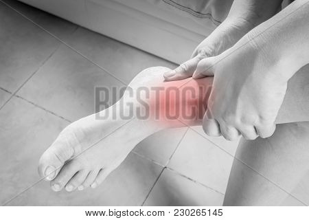 Woman With Injured Ankle  On Sofa  At Home