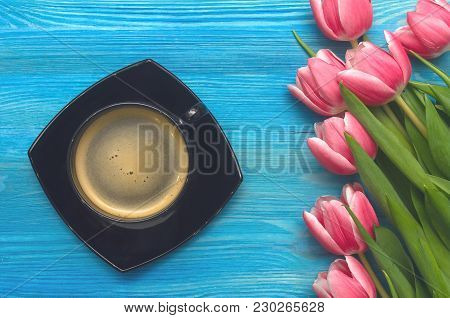 Cup Of Hot Black Coffee And Tulip Flowers On Blue Wooden Background. Romantic Breakfast Concept Back