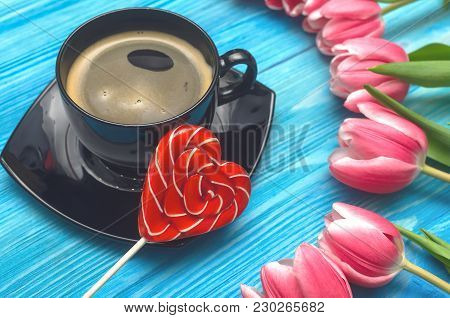 Tulip Flowers And Cup Of Hot Black Coffee With Heart Shape Lollipop Sweet On Blue Wooden Background.