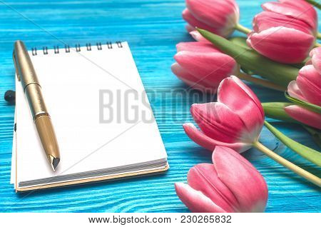 Tulip Flowers And Blank Note Pad Paper Page With Copy Space On Blue Wooden Board Background. Love Me