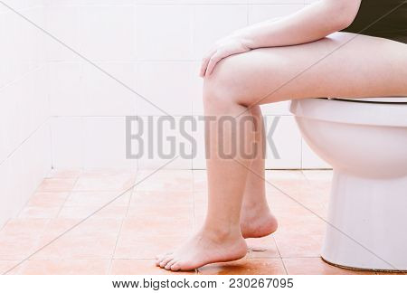 Woman Leg Is Sitting On The Toilet