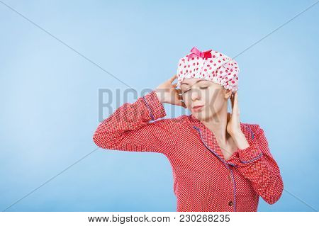 Funny Happy Woman After Shower Wearing Pink Pajamas And Dotted Bathing Cap Sitting On Bed.