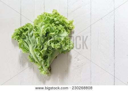 Lettuce Leaves On A White Wooden Background