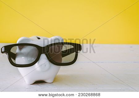 Piggy Bank With Sunglasses On Wooden Table