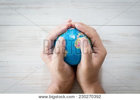 Hand Holding Model Of The Globe On Wooden Background