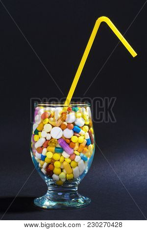 Glass Full Of Colorful Pills With Straw. Creative Composition.