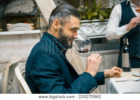 handsome bearded rich man with stylish mustache and beard holding glass and sniff smell of red wine at the restautant. tasting poster