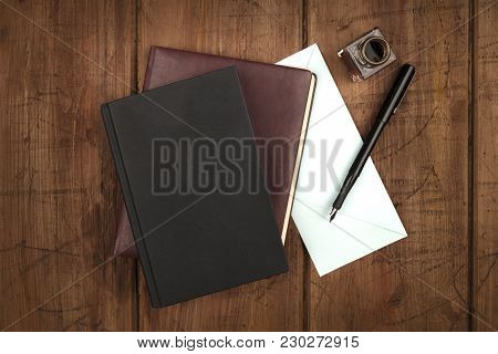 An Overhead Photo Of A Black Book, A Leather Journal, A Blue Envelope, And An Ink Well And Pen, Shot