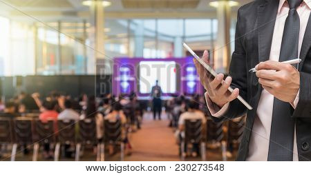 Businessman Using The Tablet On The Microphone Over The Abstract Blurred Photo Of Conference Hall Or
