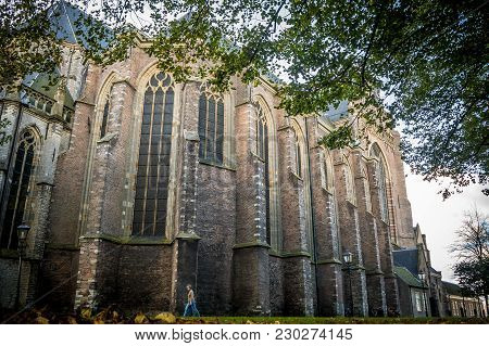 Dordrecht, Netherlands - October 27, 2017: A Woman Walks By The Old Gothic Grote Kerk On An Autumn D