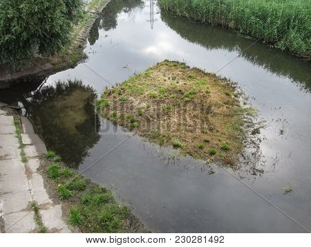 A Small Desert Island With Ducks On It In The Middle Of A Narrow River In Zaporizhia, Ukraine. Lands