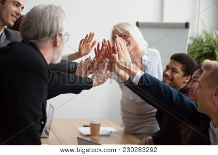 Multiracial Young And Senior Business People Join Hands Giving High Five Together, Motivated Diverse