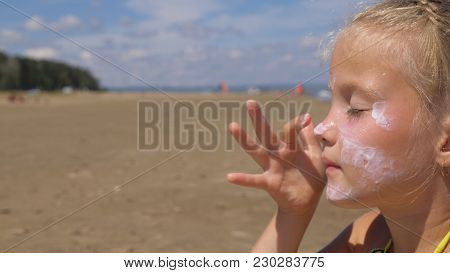 The Girl Apply Sunscreen To Face And Body. The Girl Squeezes The Sunscreen Into Her Palm And Puts It