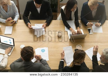 Diverse Senior And Young Business People Sitting At Conference Table Working Together Using Devices