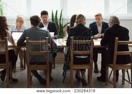 Serious Multi-ethnic Business People Team Sitting At Conference Table, Senior Executives Working Tog