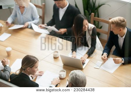 Diverse Multiracial Business Team Preparing For Group Meeting Sitting Together At Conference Table,
