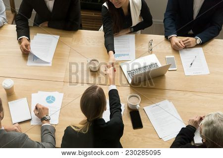 Two Businesswomen Shake Hands At Team Meeting, Female Partners Handshaking Making Deal Signing Contr