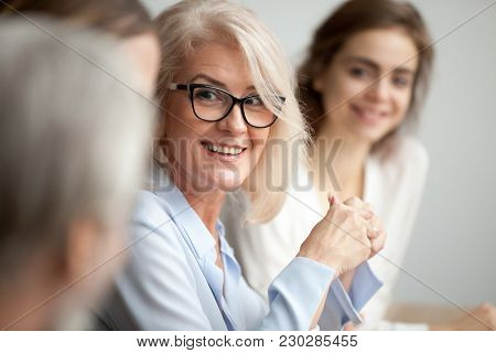 Smiling Aged Businesswoman In Glasses Looking At Colleague At Team Meeting, Happy Attentive Female T