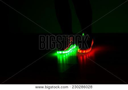 Fashionable Sneakers With Neon Led Lighting On The Legs Of A Girl With Red And Green Colors In The D